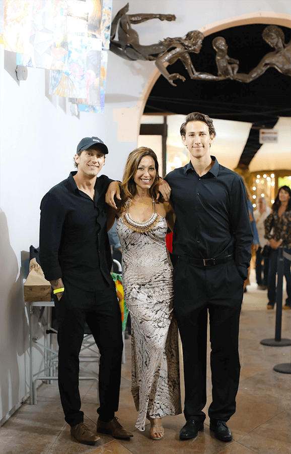 Gina posing for a photo with two gentleman at the Laguna Art A-Fair